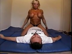 Nude female bodybuilder dominates male with scissors, facesits, ass smothers with an increment of breast